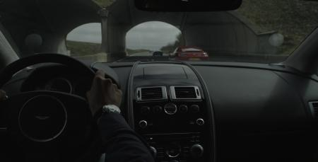 Interior picture of an Aston Martin and a Jaeger Lecoultre watch on driver's wrist