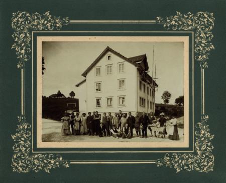 Georges-Édouard Piaget with family members and workers in front of the factory established in the former Café Français, 1911. ©Private funds